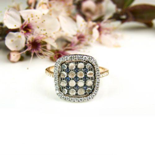 ring in roos goud gezet met diamant saffier en witte maansteen