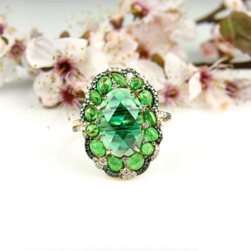 ring in roos goud gezet met groene stenen